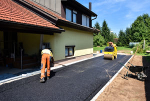 Team of workers making and constructing asphalt road