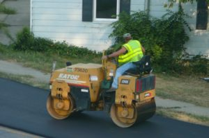 A man operating a steamroller to plain the asphalt road