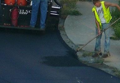 A worker repairing asphalt on the road