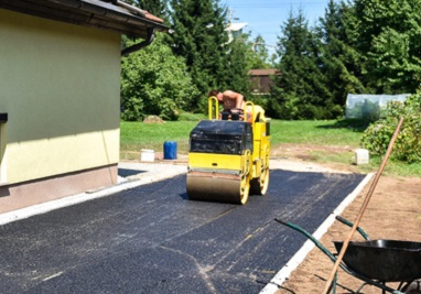 Road construction with steamroller. The top layer of asphalt road on a private residence house driveway