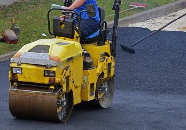 A worker leveling an asphalt road using steamroller