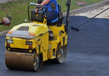 resurfacing and leveling asphalt with steamroller