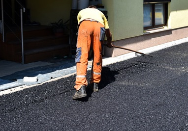 Team of Workers making and constructing asphalt road construction with steamroller. The top layer of asphalt road on a private residence house driveway